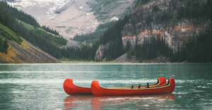 2 bright red canoes at edge of a lake